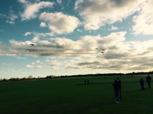 Spectators look on as the Gnat team flies past.