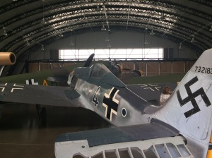 """A look inside the relocated German hangar at the Museum, which holds one of the larger aircraft the Fighter Factory looks after, the JU-52. With a static """"as recovered"""" Focke-Wulf 190 in the foreground."""