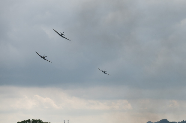 The three Spitfires diving through the smoke.