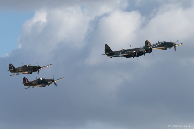Three Hurricanes are led across the Duxford sky by the Bristol Blenheim.